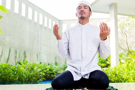 Hombre musulmán asiática que ruega en su casa sentado en la alfombra de oración en su casa frente al jardín tropical