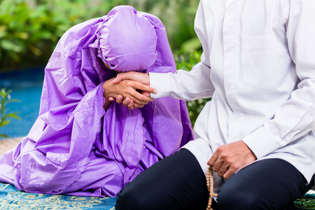 muslim pray: Asian Muslim couple, man and woman, praying at home sitting on prayer carpet in their house in front of the tropical garden Stock Photo