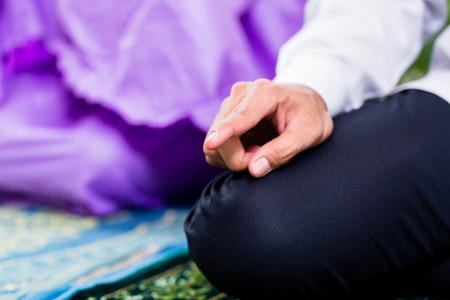 Pareja musulmán, hombre y mujer, rezando en su casa sentado en la alfombra de oración