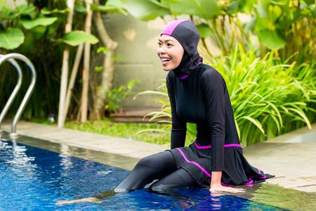 observant: Muslim woman or girl sitting at pool in tropical garden wearing Burkini halal swimwear Stock Photo