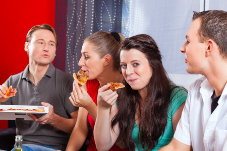 snack time: Good friends sitting together having a good time and some tasty pizza for lunch, focus on one woman