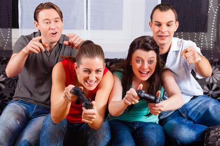 jugando videojuegos: Amigos - dos pareja - que se sientan delante de la caja de la consola de juegos y hacer tienen un montón de diversión