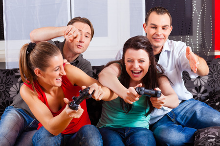 telly: Friends - two couples - sitting in front of game console box and do have lots of fun Stock Photo