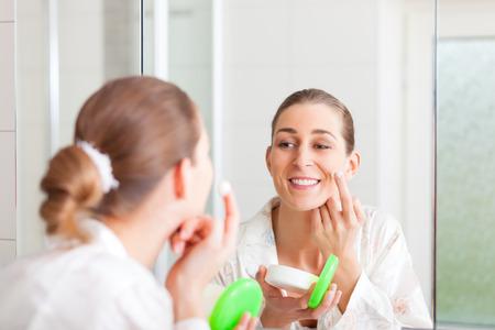 cremas faciales: Mujer joven cremas su cara delante de un espejo para mantener la piel tersa y suave Foto de archivo