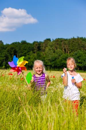 burbujas de jabon: Dos ni�os en campo jugando con pompas de jab�n y molino de viento