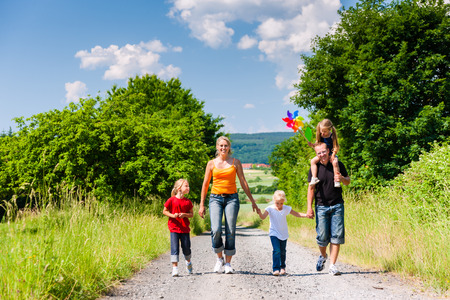 Family walking down a rural path on bright summer day photo
