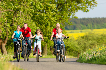 familia viaje: Familia con tres chicas tener una excursión de fin de semana en sus bicicletas o bicicletas en un día de verano en el hermoso paisaje