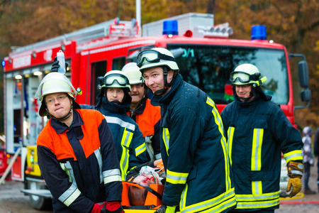 Accident - Fire brigade and Rescue team pulling cart with wounded person wearing a neck brace and respirator Stock Photo