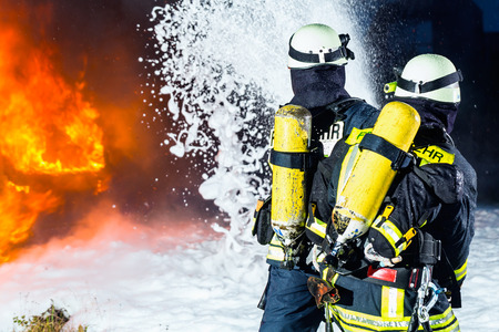 foam: Firefighter - Firemen extinguishing a large blaze, they are standing with protective wear in front of wall of fire Stock Photo