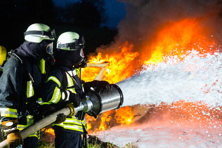 Firefighter - Firemen extinguishing a large blaze, they are standing with protective wear in front of wall of fire Stock Photo