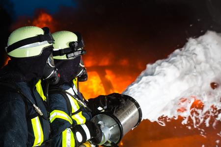 소방관 - 큰 화재를 소화 소방, 그들은 화재의 벽 앞에 보호 마모와 서