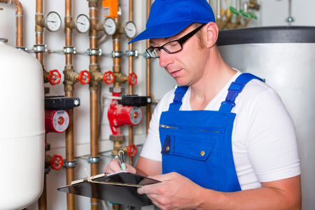 maintenance fitter: Engineer controlling the heating pipes at the boiler room Stock Photo