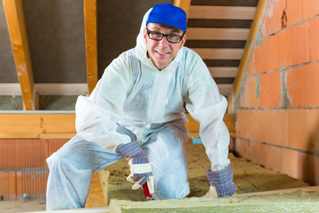 insulant: Worker in overall is cutting insulating material with gloves and knife