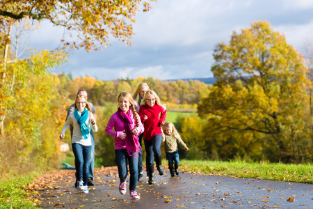 walk in: Girls running ahead at family walk through the park in fall or autumn