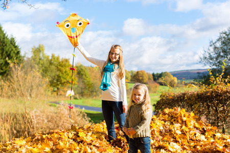 lady fly: Girls fly an kite in fall or autumn park having fun Stock Photo