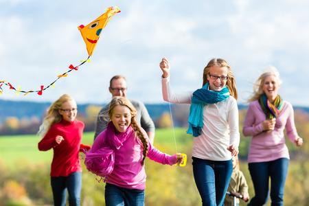 walk in: Family take walk in autumn forest flying kite