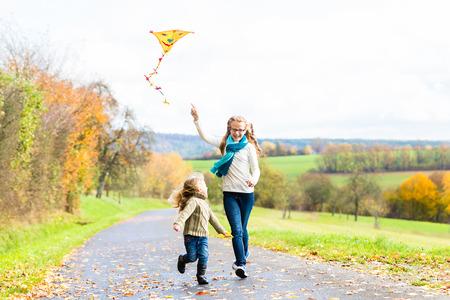 papalote: Chicas volar una cometa en el oto�o o el prado caen