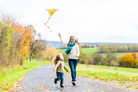 lady fly: Girls fly an kite on autumn or fall meadow Stock Photo