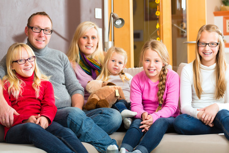 extended family: Family sitting together with mother, father and children comfortable on sofa