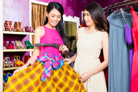 choosing clothes: Asian young sales lady offering gown to woman in fashion store