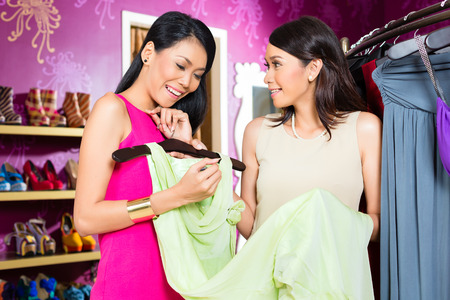 Asian young sales lady offering gown to woman in fashion store photo