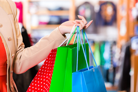 fashion bag: Woman with shopping bags in shop Stock Photo