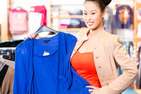 choosing clothes: Woman shopping in boutique or fashion store choosing clothes