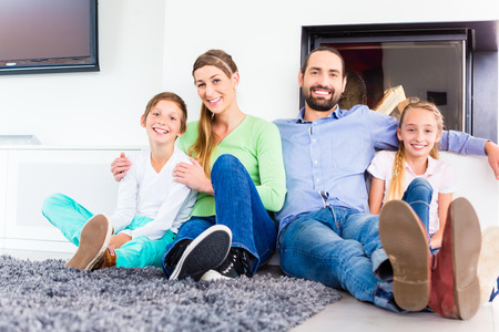 disfrutar: Familia sentado en piso de la sala de estar chimenea Foto de archivo