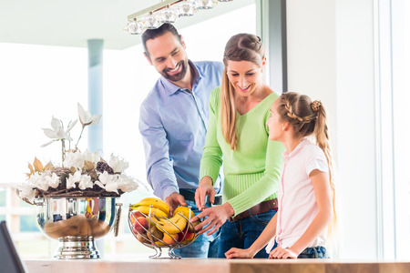 living together: Mother, father, child picking fresh fruits for healthy living in home kitchen