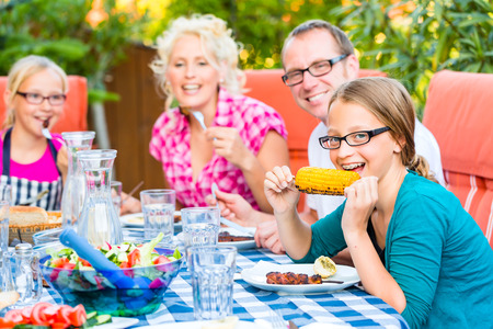 Family at eating in garden summer barbecue