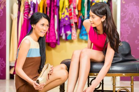 comprando zapatos: Señora asiática de ventas joven ofreciendo zapatos de mujer en tienda de moda