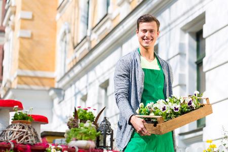 flower bed: Young handsome florist delivering palette of flowers or viola Stock Photo