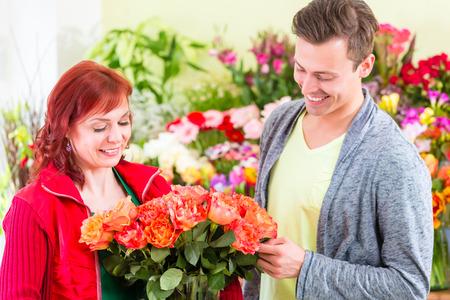 Female florist selling man flowers in flower shop photo