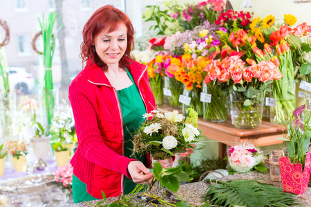 florist shop: Female florist binding flower bouquet in shop
