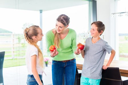 vital: Mother giving children fresh fruits for healthy living Stock Photo
