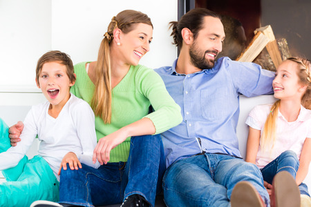 fireplace living room: Family sitting at living room floor fireplace Stock Photo