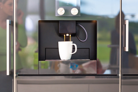 Fully automatic coffee machine in modern domestic kitchen