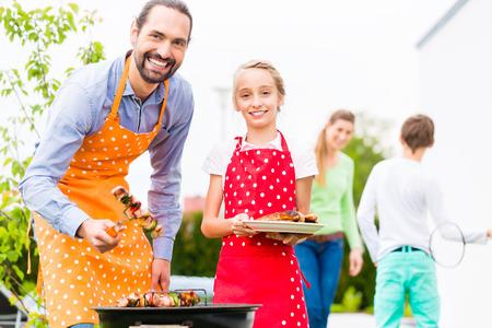 famiglia in giardino: Padre e figlia barbecue spiedi di carne e salsicce alla famiglia giardino barbecue