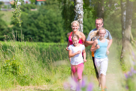 Family running for better fitness in summer through beautiful landscape Stock Photo