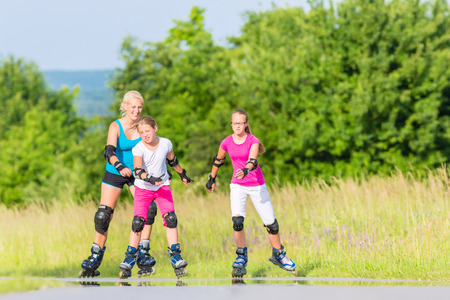 inline skating: Mother and daughters rollerblading with in-line skates on country lane