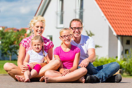 homestead: Family of Parents and children sitting proud in front of suburban home Stock Photo
