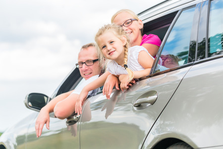 woman driving: Family car - Father driving with daughters in auto