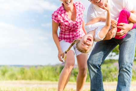 Family romping on field with parents carrying child photo