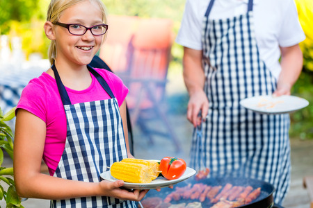 Family of Father and daughter barbecue meat and corncobs at family garden BBQ Stock Photo