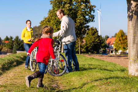 Family with mother, father and daughter having family trip on bicycle or cycle in park or country photo