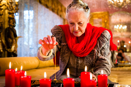 seance: Female Fortuneteller or esoteric Oracle, sees in the future by dowsing her pendulum during a Seance to interpret them and to answer questions