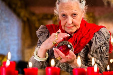 esoterismo: Fortuneteller Mujer o esotérica Oracle, ve en el futuro mirando en su bola de cristal Foto de archivo