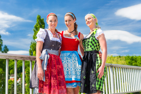 Friends visiting together Bavarian fair in national costume or Dirndl photo