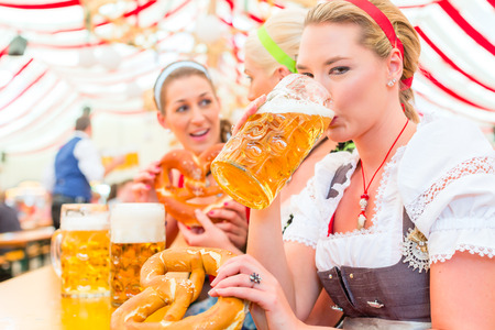 Women drinking Bavarian beer in tent on Oktoberfest or dult wearing dirndl photo