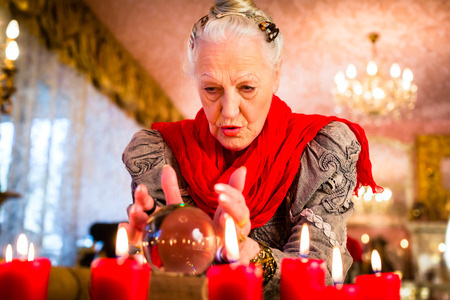 interpretation: Female Fortuneteller or esoteric Oracle, sees in the future by looking into their crystal ball during a Seance to interpret them and to answer questions Stock Photo